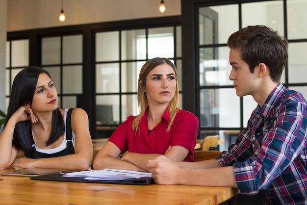 Portrait von drei jungen kollegen oder von studenten, die diskussion haben