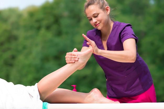 Portrait von frauentherapeutin, masseurin, massagetherapeutin, die massage von beinen, weiblichen füßen, fuß mit öl im freien macht. professioneller physiotherapeut. dame liegt und entspannt. natürlicher hintergrund.
