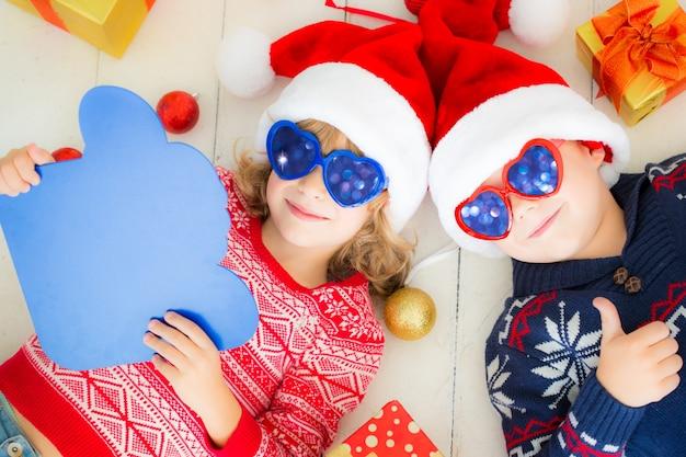 Portrait von glücklichen kindern mit weihnachtsschmuck. zwei kinder haben spaß zu hause