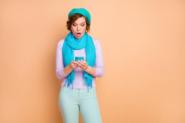 Portrait von ihr, sie ist ein hübsches, attraktives, hübsches, nervöses, besorgtes, süchtiges mädchen, das das gerät verwendet, das smm-fake-news einzeln auf beige pastellfarbenem hintergrund durchsucht