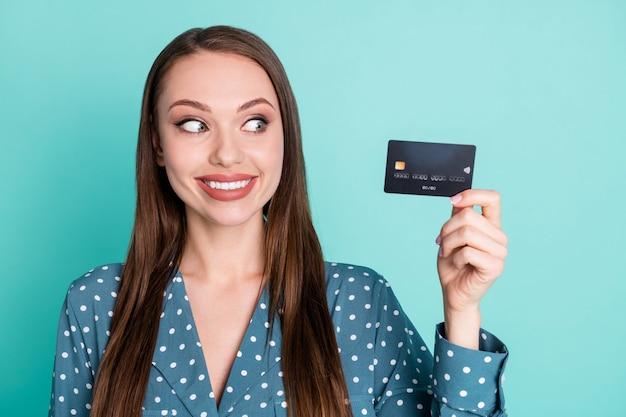 Portrait von positiv fröhlichen mädchen halten look kreditkarte tragen polka-dot retro-bluse isoliert auf blaugrünem hintergrund