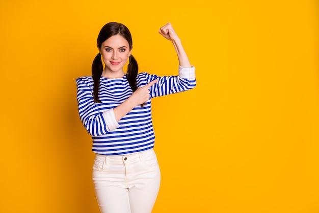 Portrait von positivem, fröhlichem, charmantem mädchen, das zugsport-aufwärmtraining zeigt, trizeps-punkt-zeigefinger tragen gut aussehende bluse isoliert heller glanzfarbhintergrund