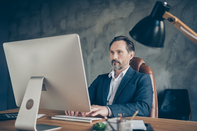Portrait von seinem schönen attraktiven, gutaussehenden, fokussierten, qualifizierten mann hai-experte it-programmierer, der e-mail schreibt e-banking-kundendienst betonindustriewand-arbeitsplatzstation