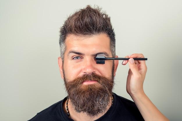 Portrait von sexy mann mit bart-modell gesicht und pinzette in der nähe von brauen. schönheitskonzept. augenbrauenkorrektur. nahaufnahme des schönen lustigen mannes, der augenbrauen zupft. hohe auflösung