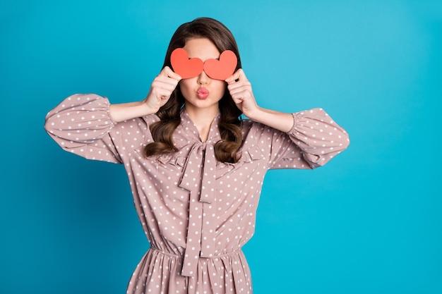 Portrait von traum süße schöne liebesmädchen halten kleine rote papierkarte herz schließen deckelaugen senden luftkuss tragen gut aussehende kleidung einzeln auf blauem hintergrund