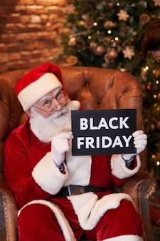 Portrait von zufriedenen senior santa claus in gläsern sitzend mit schwarzem freitagsbanner gegen weihnachten...