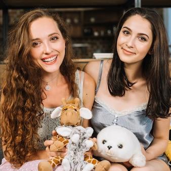 Portrait von zwei freundinnen mit weichem spielzeug