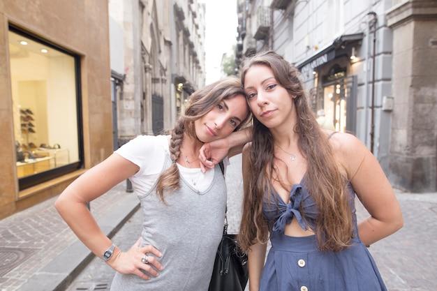 Portrait von zwei weiblichen freunden, die in der straße stehen