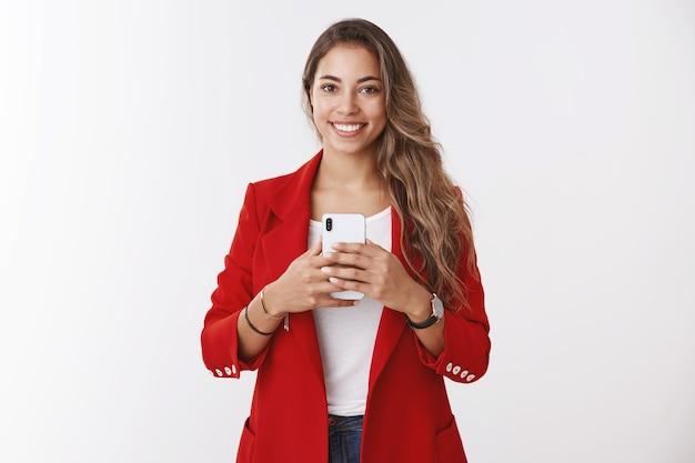 Portrait wunderschöne selbstbewusste, stilvolle frau mit roter jacke, die bittet, ein foto zu machen, das ein smartphone hält, das breit lächelt, wie ein selfie-spiegel, der ein gutes outfit sieht und bilder online veröffentlicht