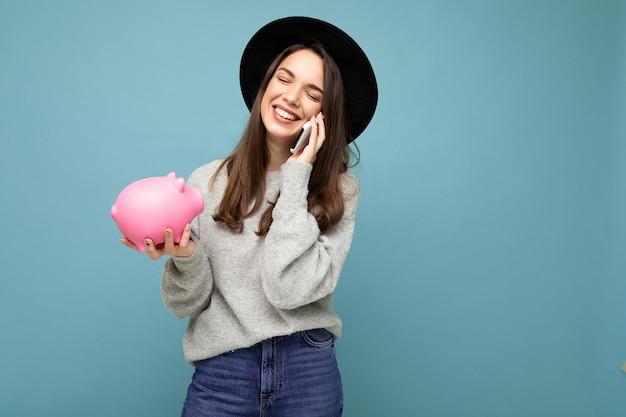 Portraitfoto der glücklichen positiven lächelnden jungen attraktiven brünetten frau, die beiläufigen grauen pullover trägt