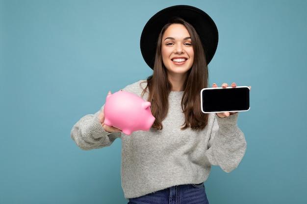 Portraitfoto der glücklichen positiven lächelnden zufriedenen aufrichtigen jungen attraktiven brünetten frau, die trägt Premium Fotos