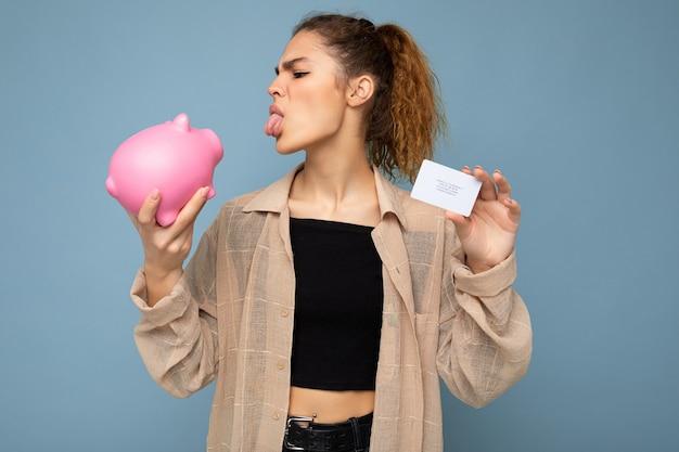Portraitfoto einer positiven, lustigen, unzufriedenen jungen, schönen, brünetten, lockigen frau mit aufrichtigen emotionen, die ein stylisches beige hemd trägt, isoliert auf blauem hintergrund mit kopierraum, hält rosa sparschwein