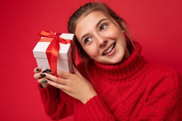 Portraitfoto einer ziemlich positiven, nachdenklichen, brünetten jungen frau, die über einer roten hintergrundwand isoliert ist und einen roten pullover trägt, der weiße geschenkbox mit rotem band hält und zur seite schaut.