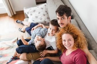 Porträt der Familie zu Hause sitzend auf Sofa