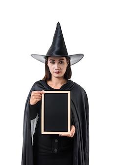 Porträt der Frau im schwarzen beängstigenden Hexe Halloween-Kostüm, das mit Hut steht, lokalisierte Weiß
