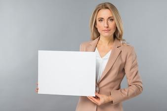 Porträt der jungen Geschäftsfrau leeres weißes Plakat gegen grauen Hintergrund zeigend