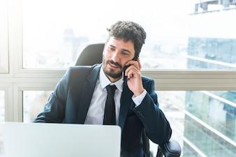 Porträt des jungen Geschäftsmannes sprechend am Handy nahe dem Fenster