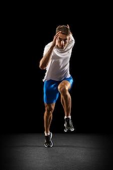 Portrat des kaukasischen professionellen männlichen athleten, läufertraining isoliert auf schwarz