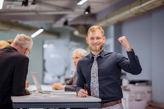 Porträt des lächelnden Geschäftsmannes seine Faust zusammenpressend während das Team, das im Hintergrund sich bespricht