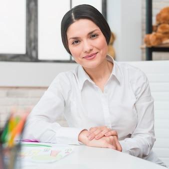 Porträt des lächelnden professionellen weiblichen Psychologen, der in ihrem Büro sitzt