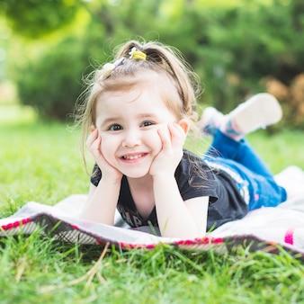 Porträt des lächelnden schönen Mädchens, das auf Decke im Garten liegt