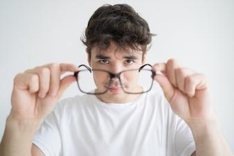 Porträt des starken jungen Studenten, der Brillen betrachtet