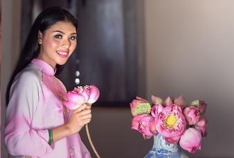 Porträt des vietnamesischen Mädchentrachtenkleides mit Lotos