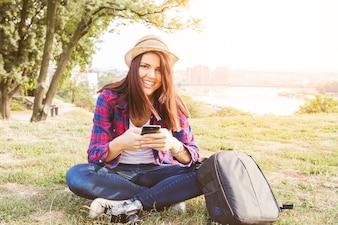 Porträt einer glücklichen jungen Frau, die Handy im Park hält