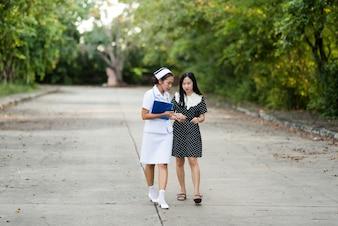 Porträt einer jungen Krankenschwester, die einen weißen Hut trägt