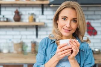 Porträt einer lächelnden jungen Frau, die in der Hand weißen Tasse Kaffee hält