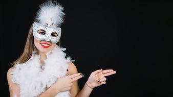 Porträt einer lächelnden tragenden Karnevalsmaske der Frau, die auf weißen Hintergrund gestikuliert