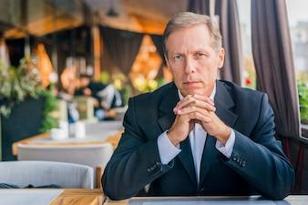 Porträt eines ernsten Mannes, der im Restaurant sitzt
