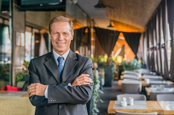 Porträt eines glücklichen erfolgreichen Geschäftsmannes, der im Restaurant mit dem gekreuzten Arm steht