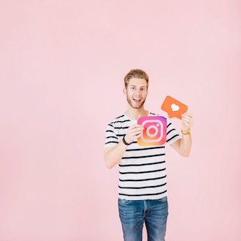 Porträt eines glücklichen jungen Mannes, der instagram hält und mögen Ikone