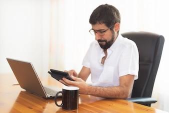 Porträt eines hübschen Hippie-Kerls, der im Büro arbeitet