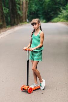Porträt eines Mädchens, das auf Stoßroller an der Straße steht