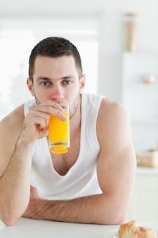Porträt eines Mannes, der Orangensaft in seiner Küche trinkt