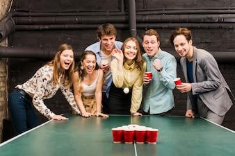 Porträt eines Mannes und der Freundinnen, die Bier Pong auf Tabelle spielen