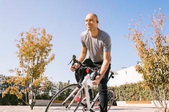 Porträt eines männlichen Radfahrers, der auf dem Fahrrad weg schaut sitzt