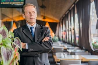 Porträt eines reifen Geschäftsmannes mit den gekreuzten Armen, die im Restaurant stehen