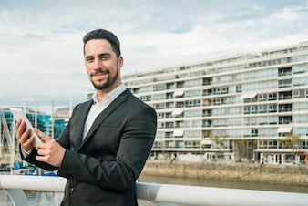 Porträt eines überzeugten jungen Mannes, der in der Hand den Handy betrachtet Kamera hält
