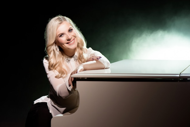 Portret des pianisten, der in der nähe des weißen klaviers auf der bühne im lichtstrahl aufwirft.