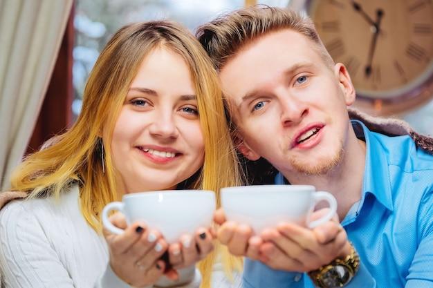 Portret junges glückliches romantisches paar, das im café sitzt und händchen hält