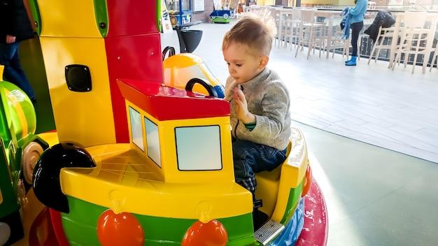 Portriat eines fröhlichen kleinkindjungen, der auf einem bunten karussell mit spielzeugbooten im vergnügungspark im einkaufszentrum reitet?