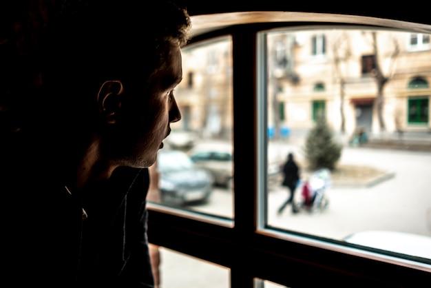 Portriat oder schattenbild des jungen mannes sitzend vor fenster