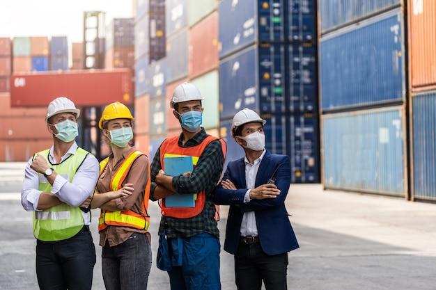 Portrit-arbeitermann, der einen laptop verwendet, der eine chirurgische maske und einen weißen sicherheitskopf zum schutz vor verschmutzung und viren am arbeitsplatz während der besorgnis über eine covid-pandemie verwendet