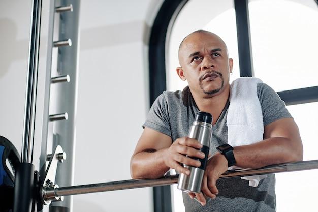Portrtait von müde nachdenklich fit mann trinkwasser und ruhe nach dem training mit schweren gewichten in modernen fitnessstudio
