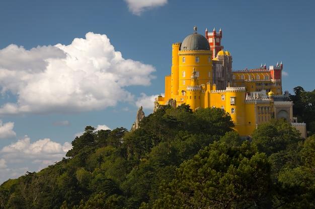 Portugal. sintra. der pena-palast auf einer klippe, umgeben von wald und wolken