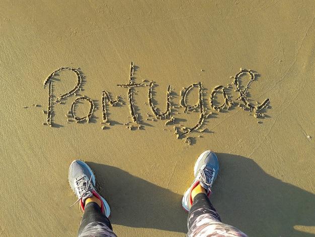 Portugal-text in den sand von hand geschrieben. füße von oben am strand