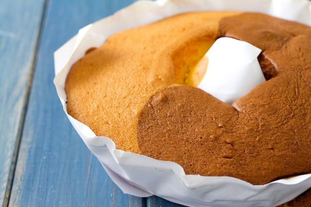 Portugiesischer kuchen pao de lo auf weißbuch auf blauer holzoberfläche